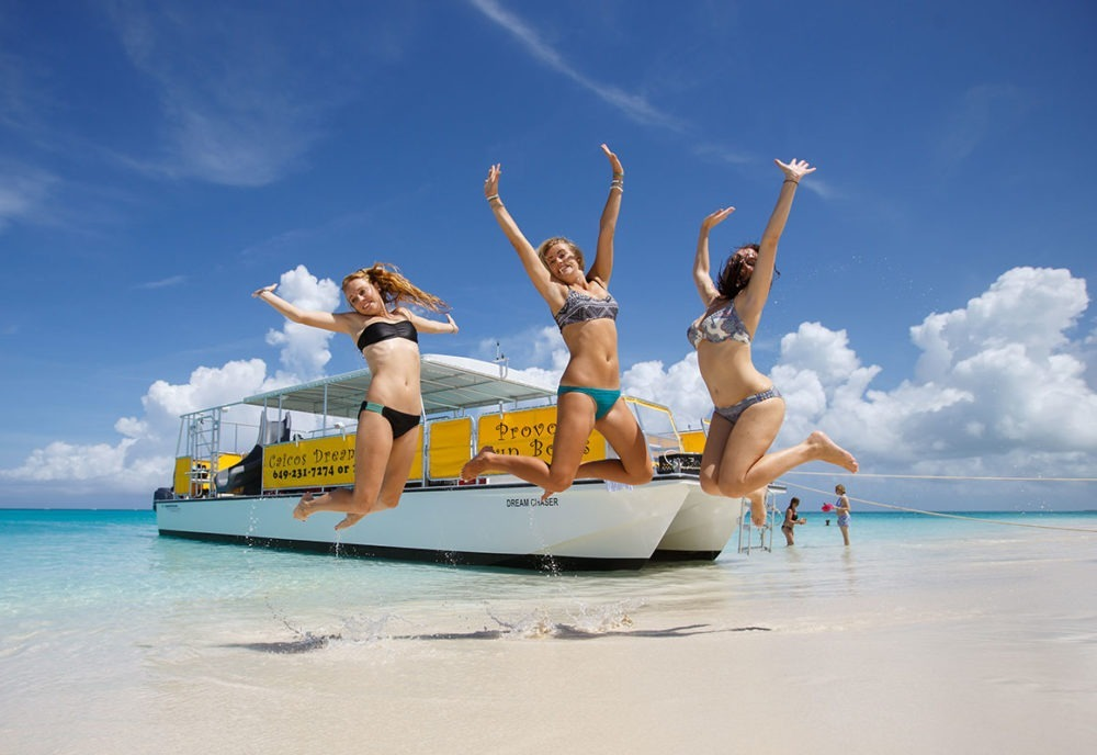 friends jumping in front of caicos dream tour boat