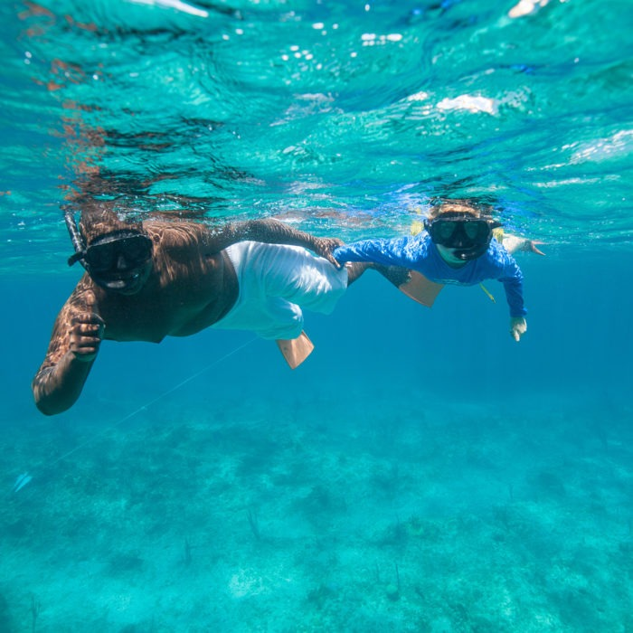 Father and Child snorkeling in clear reef water